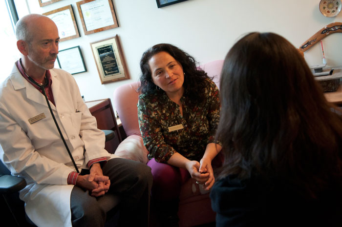Medical and counseling staff talk together with a patient