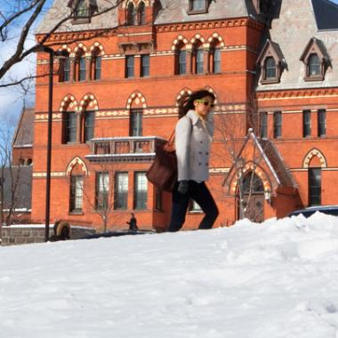 Student walking by Sage Hall with snow in foreground