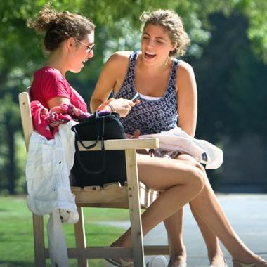 Students talking on a bench outside in summer